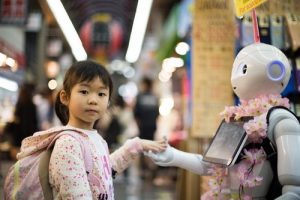 Little girl holding hands with a robot at a gadgets store